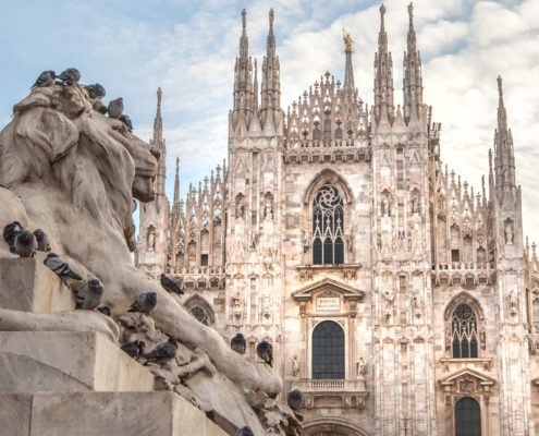 Milano Duomo with a lion statue in the foreground