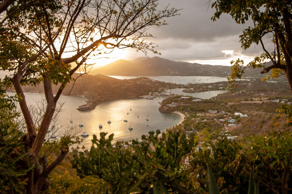 Sunset view from high up in Antigua at Shirley Heights, an old fort looking down on a harbour with boats