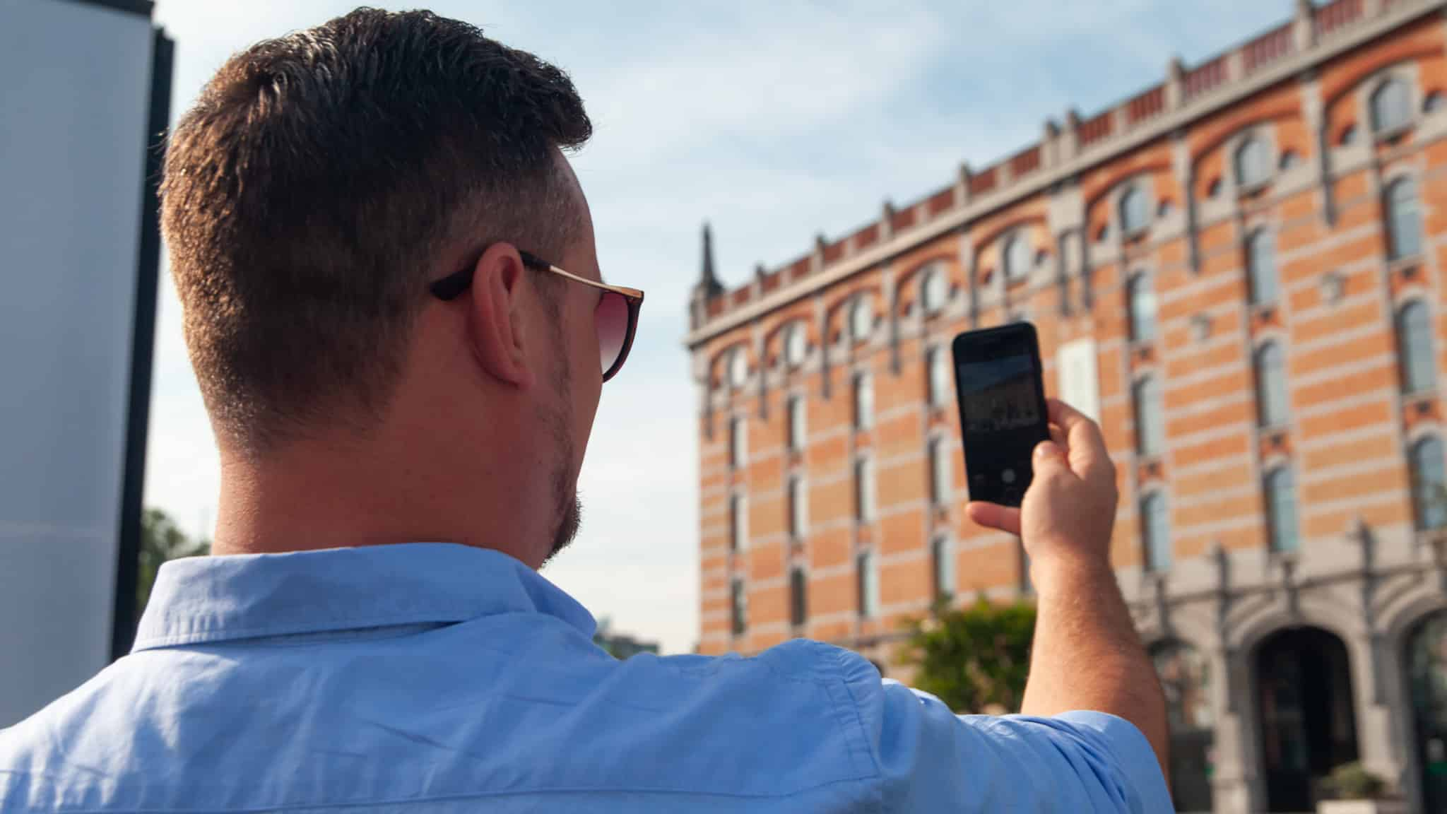 Dan using a mobile phone to take a photo in Brussels