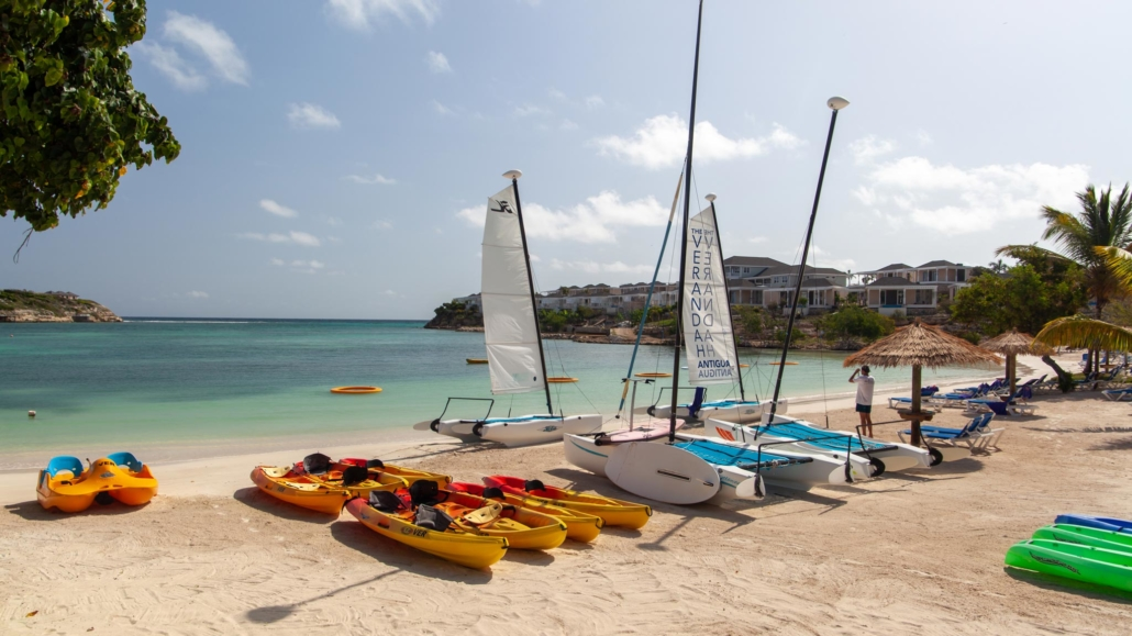 Kayaks and sail boats lined up on a beach in Antigua