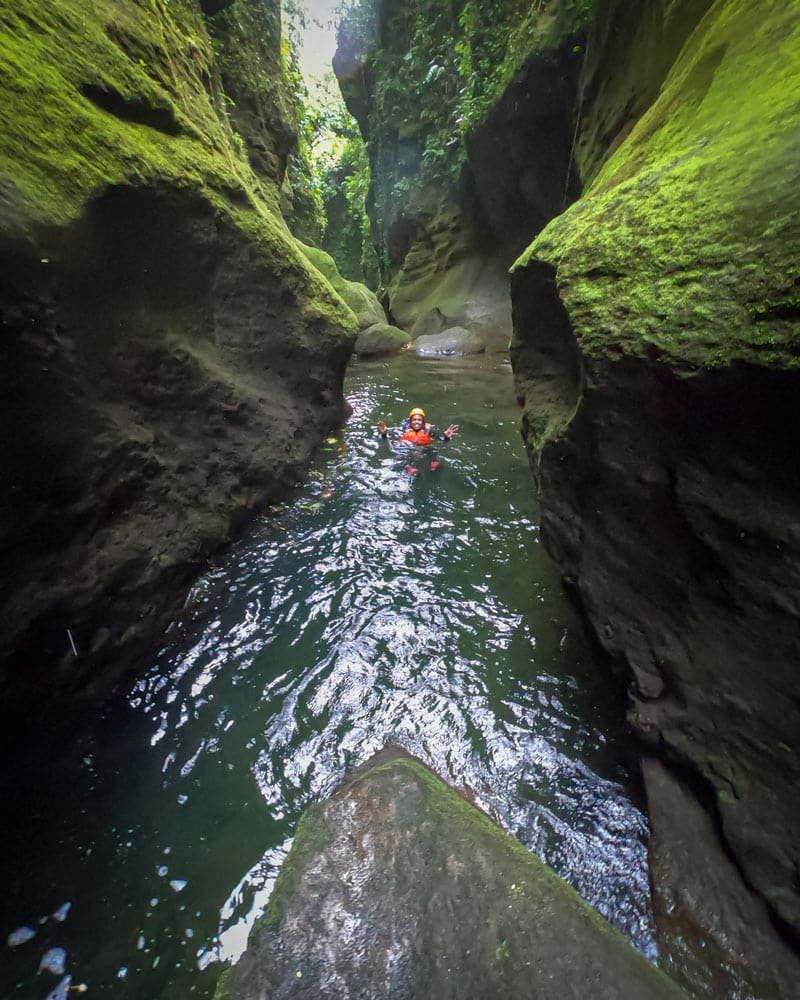 A pool of water with a person at the bottom of a canyon in Dominica