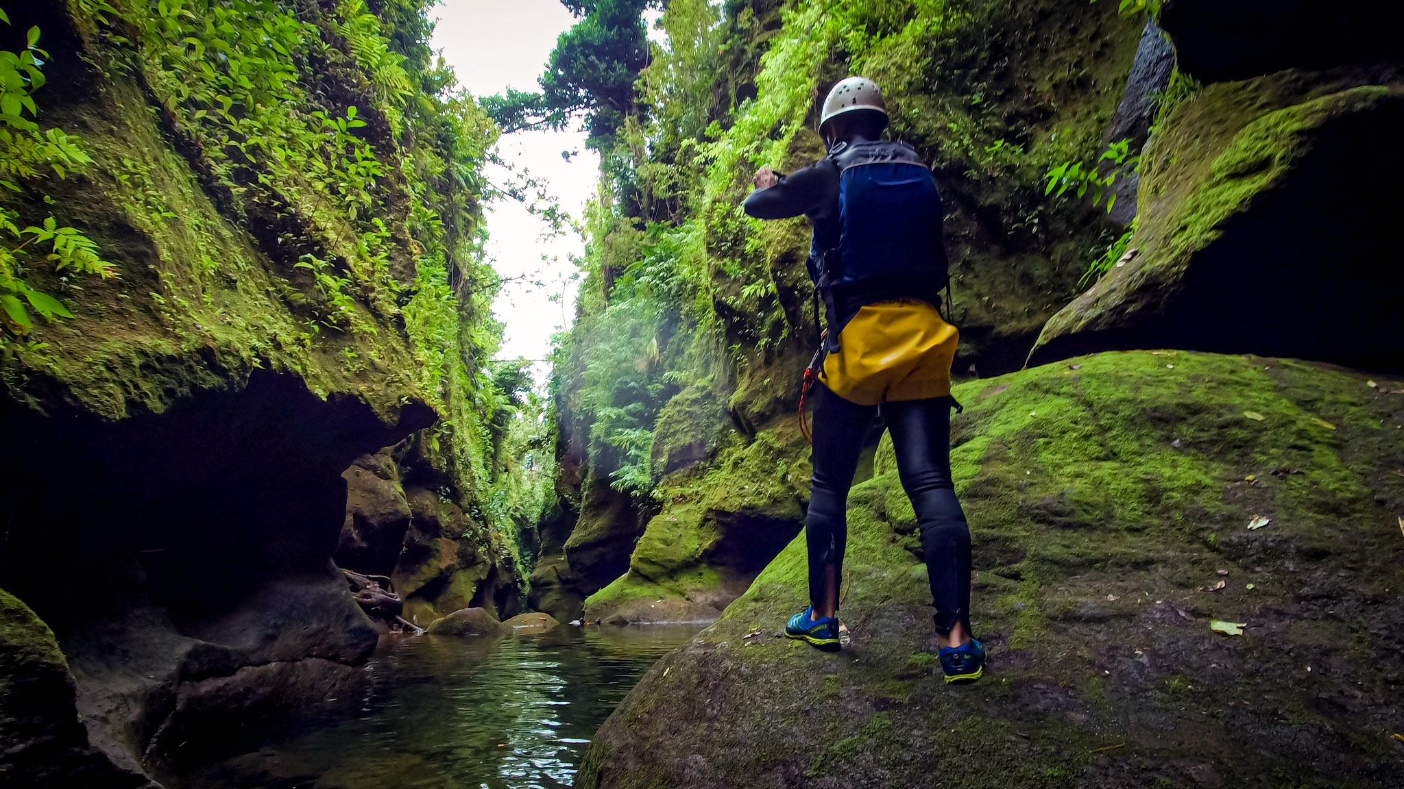 A man stands in a green moss covered canyon taking a photo in Dominica