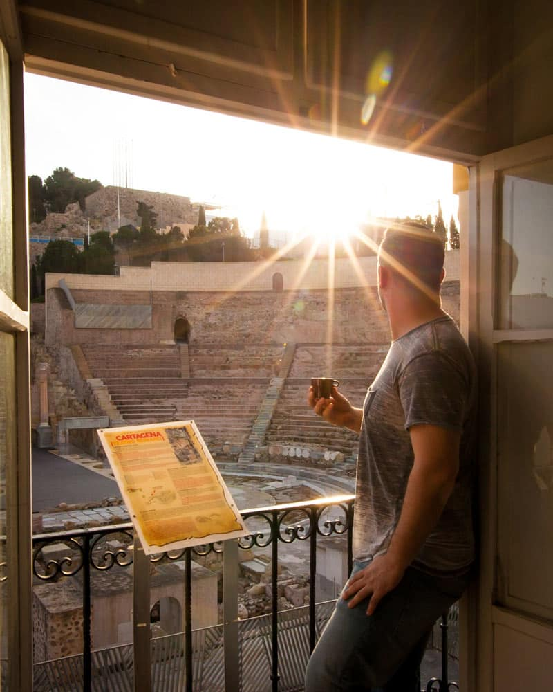 Dan in the window of an apartment looking out on the Roman Theatre