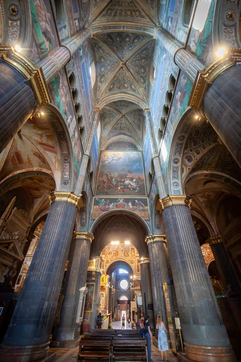 Inside Cremona Cathedral, towering pillars lead to the arched ceiling