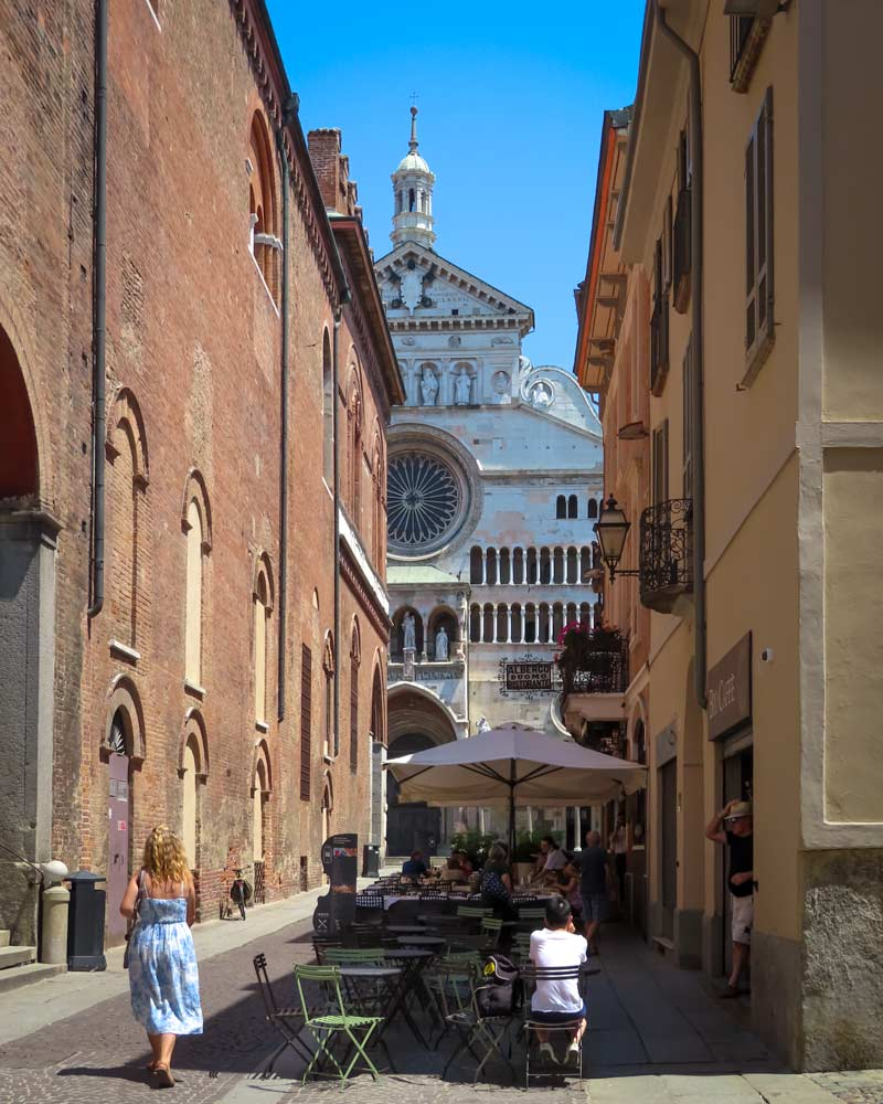The Cremona Cathedral framed by a restaurant on one side and the town hall on another