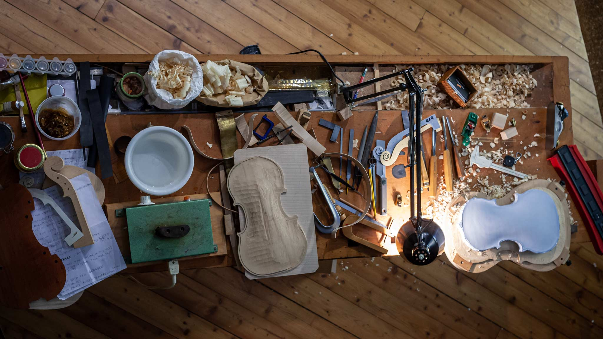 Looking down on a table where Violins are made full of various tools in Cremona