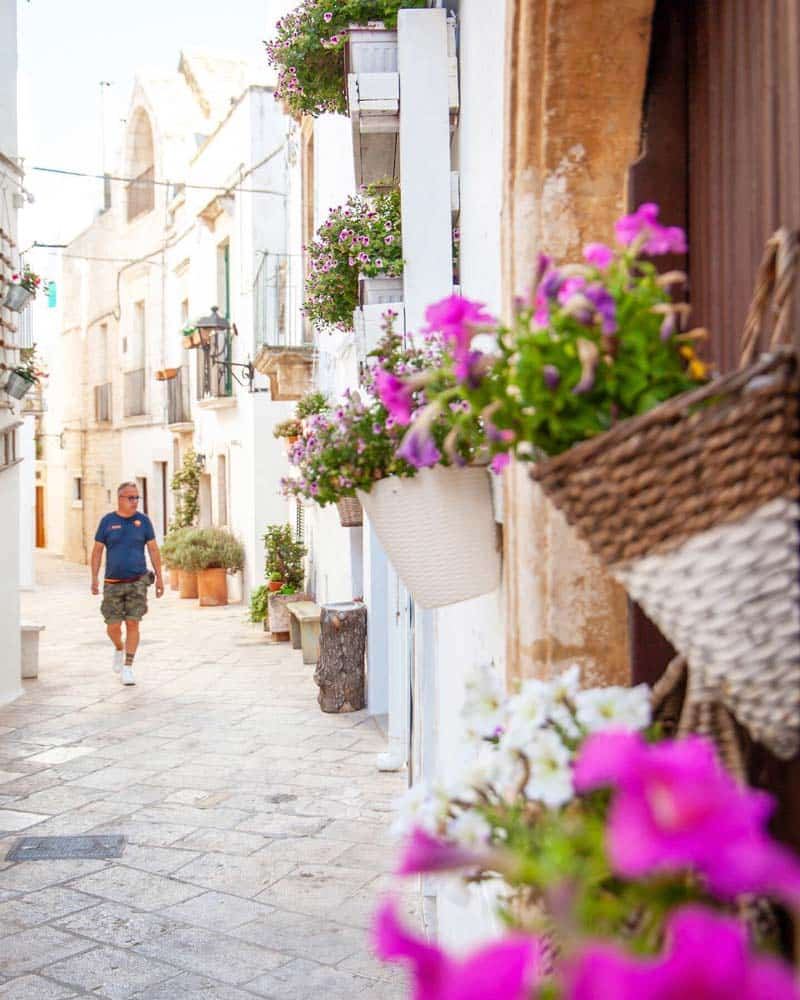 Locorotondo Puglia with white washed streets and pink flowers