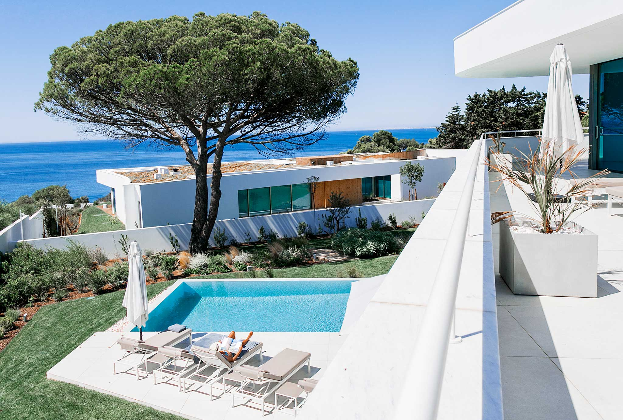 Looking out on the Atlantic ocean and an infnity pool with two white luxury villas in the picture at Lux Mare
