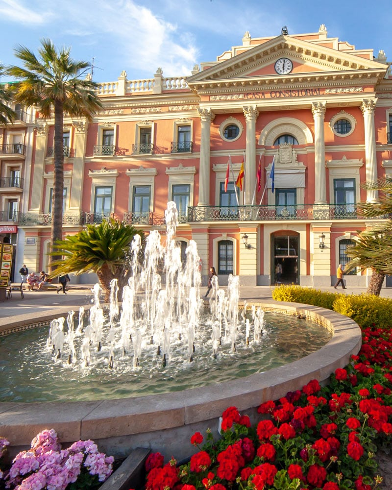 A pink building and a water fountain with palm trees in Murcia Spain