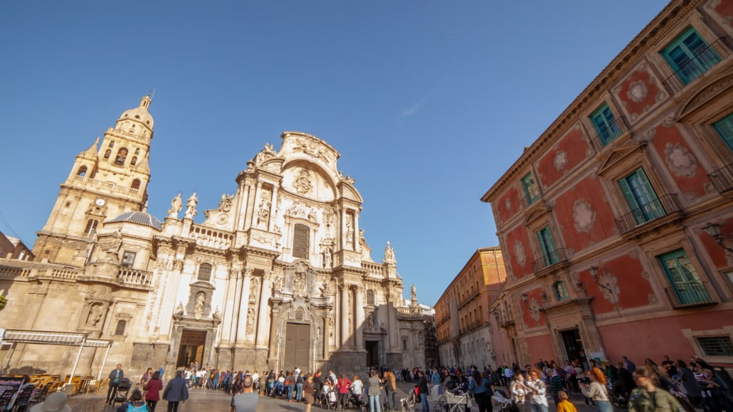 The main square in Murcia with a cathedral on the left and a red fronted palace on the right