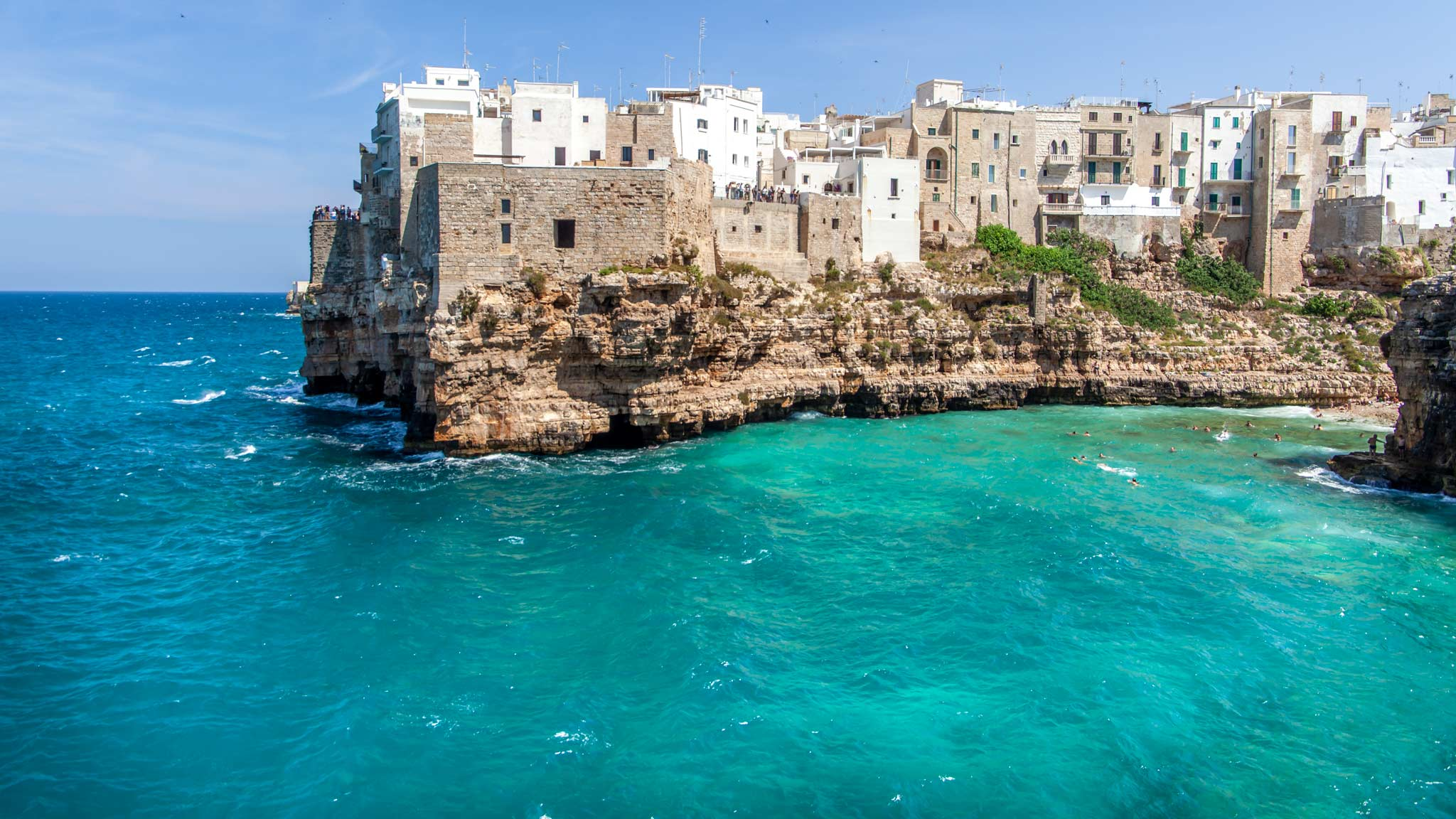 The white-washed cliff buildings stick out over the blue ocean of Polignano a Mare