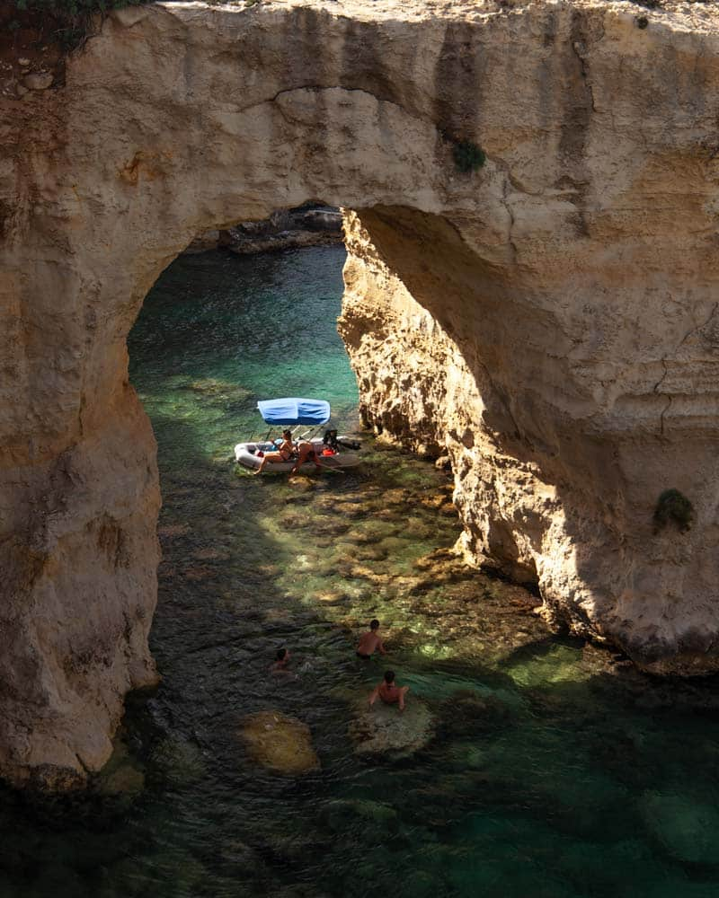 Sun comes through a cave on the Puglia coastline