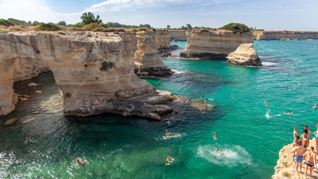 Blue hued waters crash into rocks jutting out of the Puglia coastline