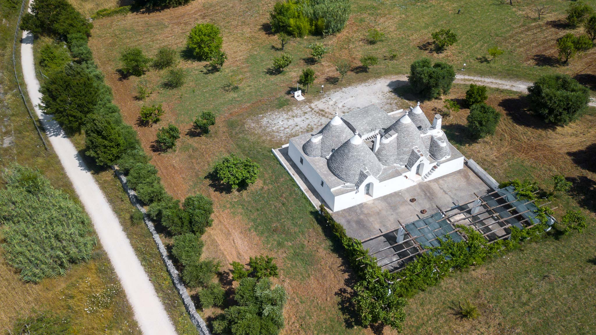 A Trulli house hotel as seen from above surrounded by olive trees