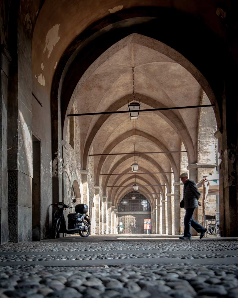 A man walks through a covered archway in Bergamo Lombardy
