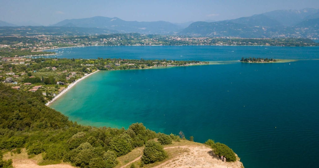 Lake Garda seen from above high up on a hill looking out on a beach and islands