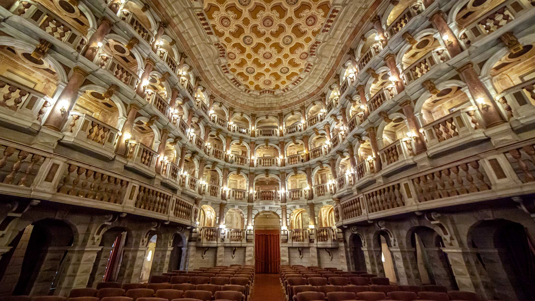 A grand theatre, looking out from the stage to the stools and boxes in Mantua