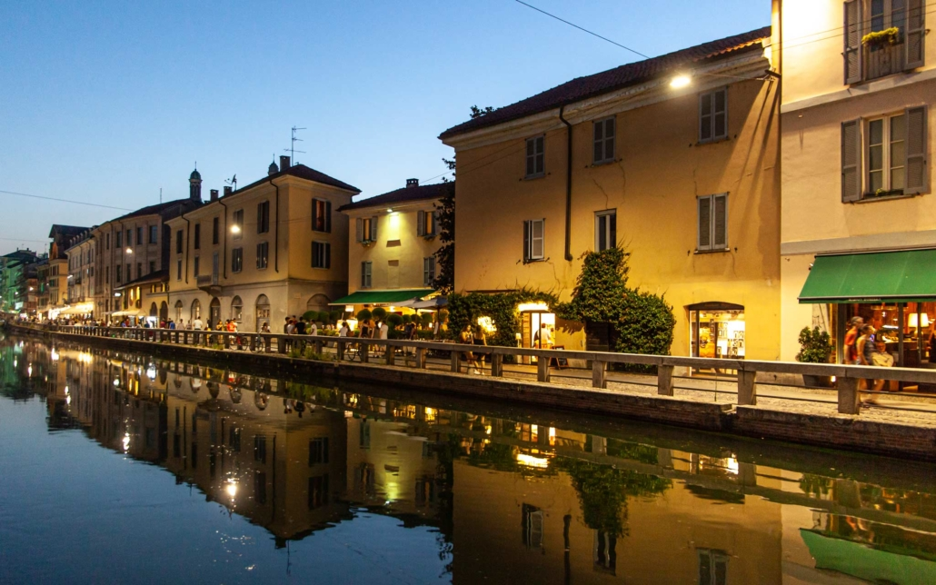 Canals reflect the shops and homes in Milan