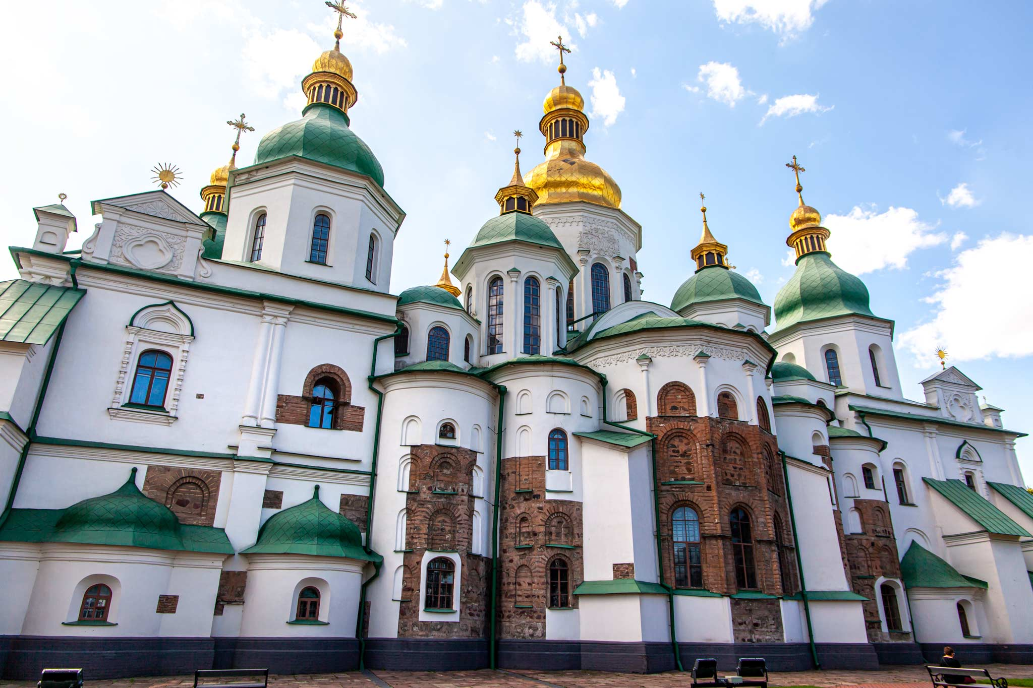 A green and white Kyiv orthodox cathedral with gold domes on the roof