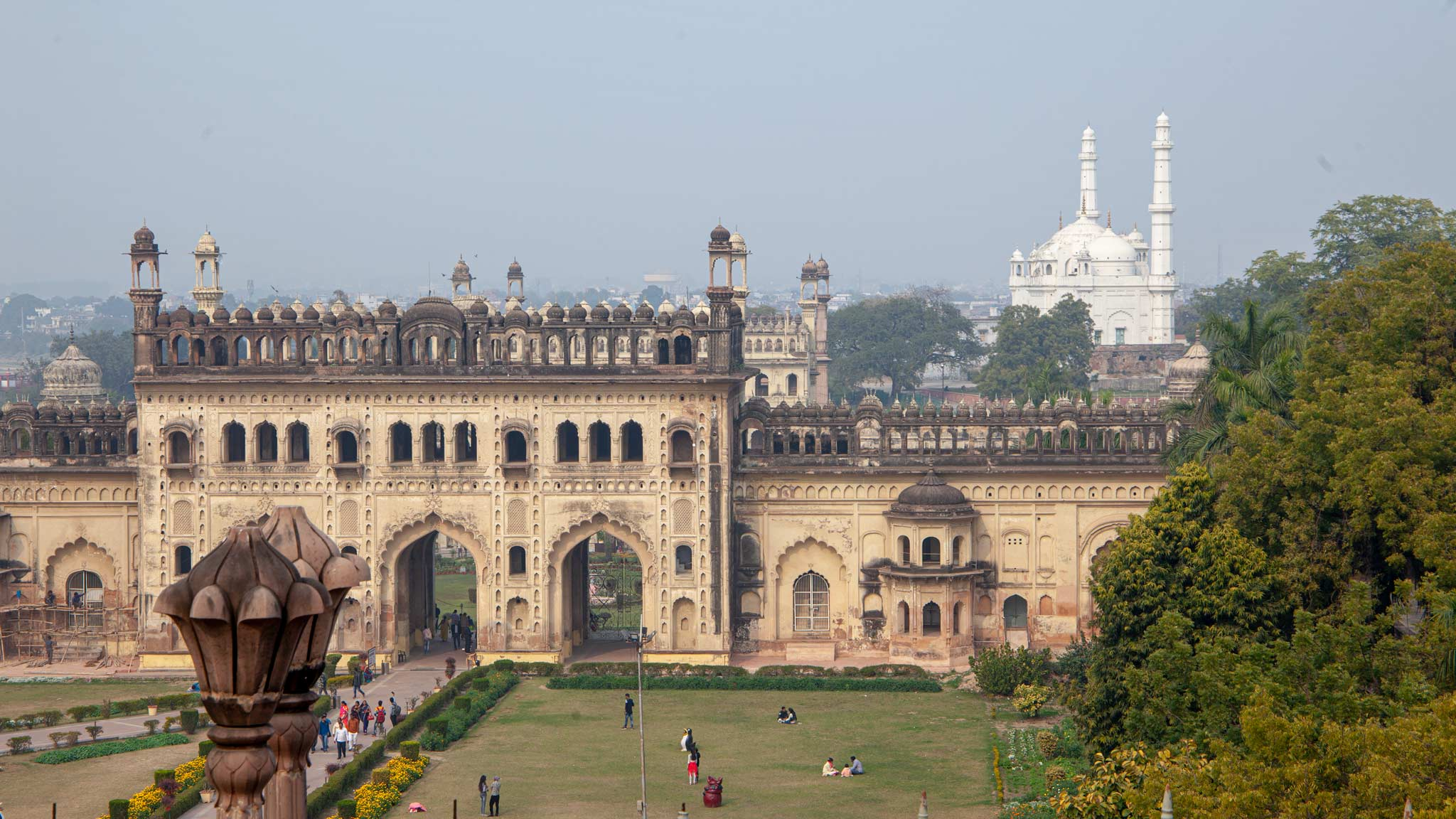 The Bara Imambara main entrance is a large building in Lucknow with archways, in the distance is a white mosque