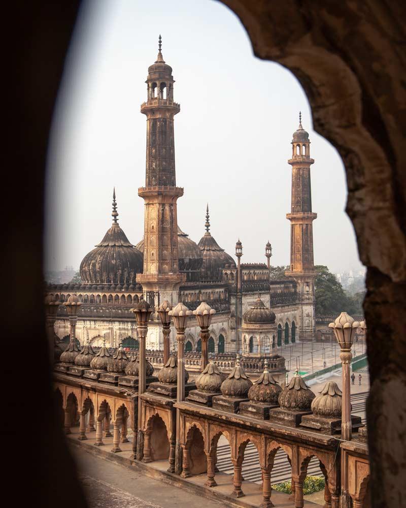 The Bara Imambara mosque with three minarets as seen through a window