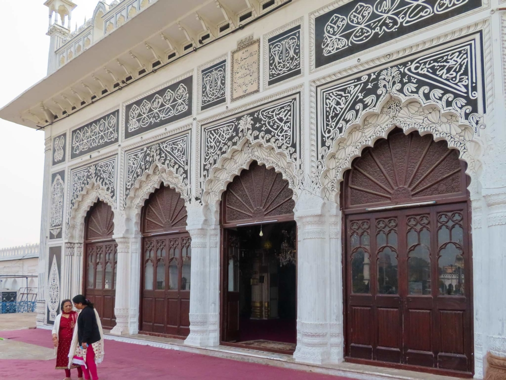 Arched door ways with intricate islamic design are met by a red carpet where two ladies talk