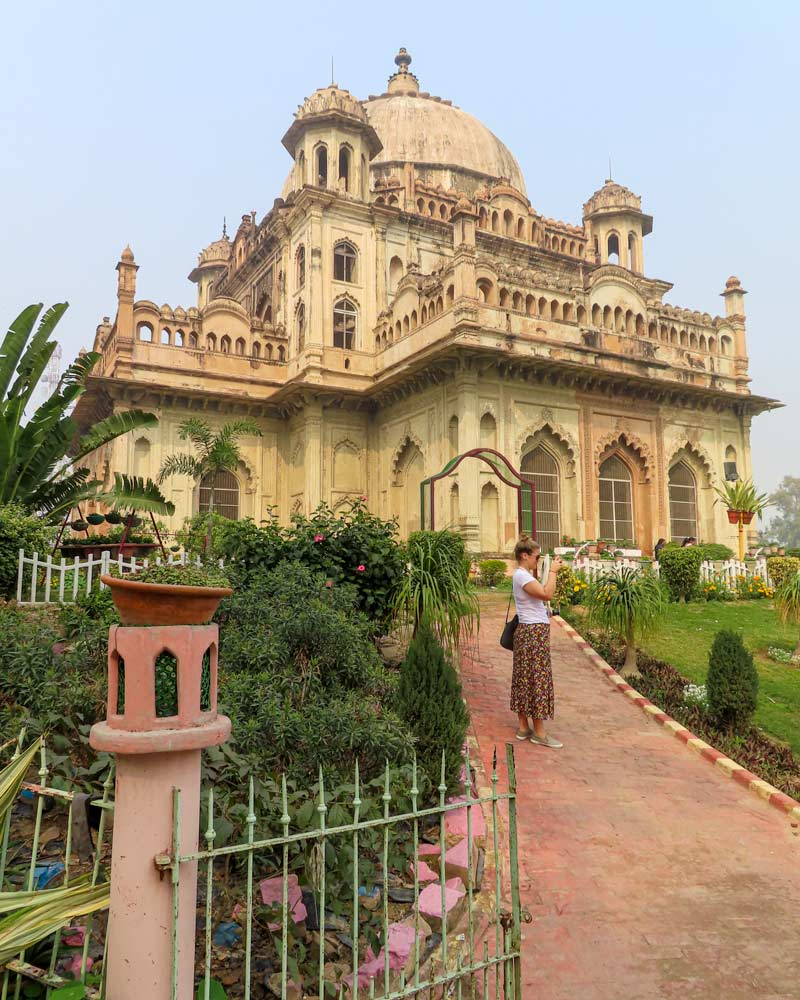 A lady stands infront of an old building in Lucknow Delhi surrounded by verdant gardens