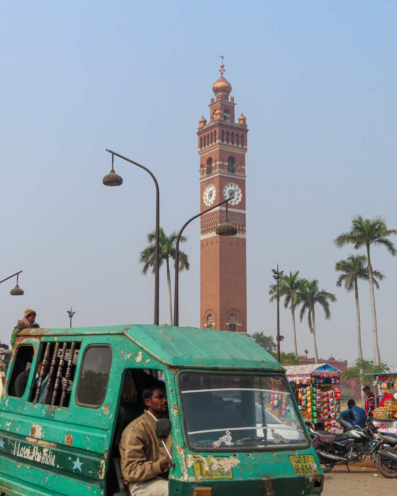 The Ghanta Ghar is a clocke tower which stands behind a green minibus