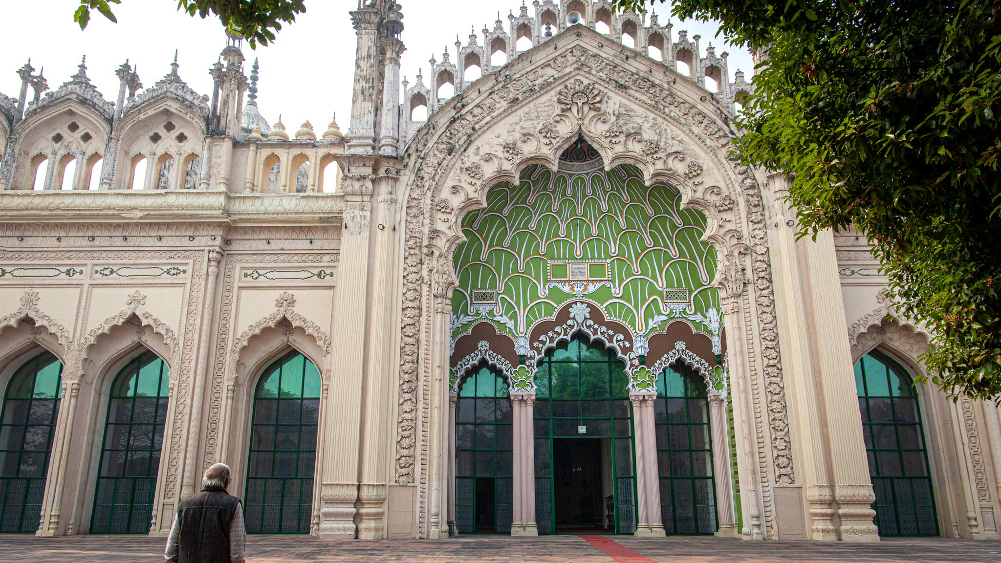 The entrance gate to Jama Masjid Mosque in Lucknow, where a man stands praying to the left and various archways with colourful tiles are on the building