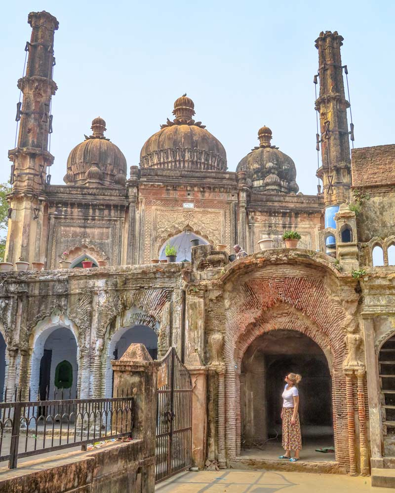 The old mosque in the Residency Lucknow with a girl standing in the archway looking up at the domed roofs