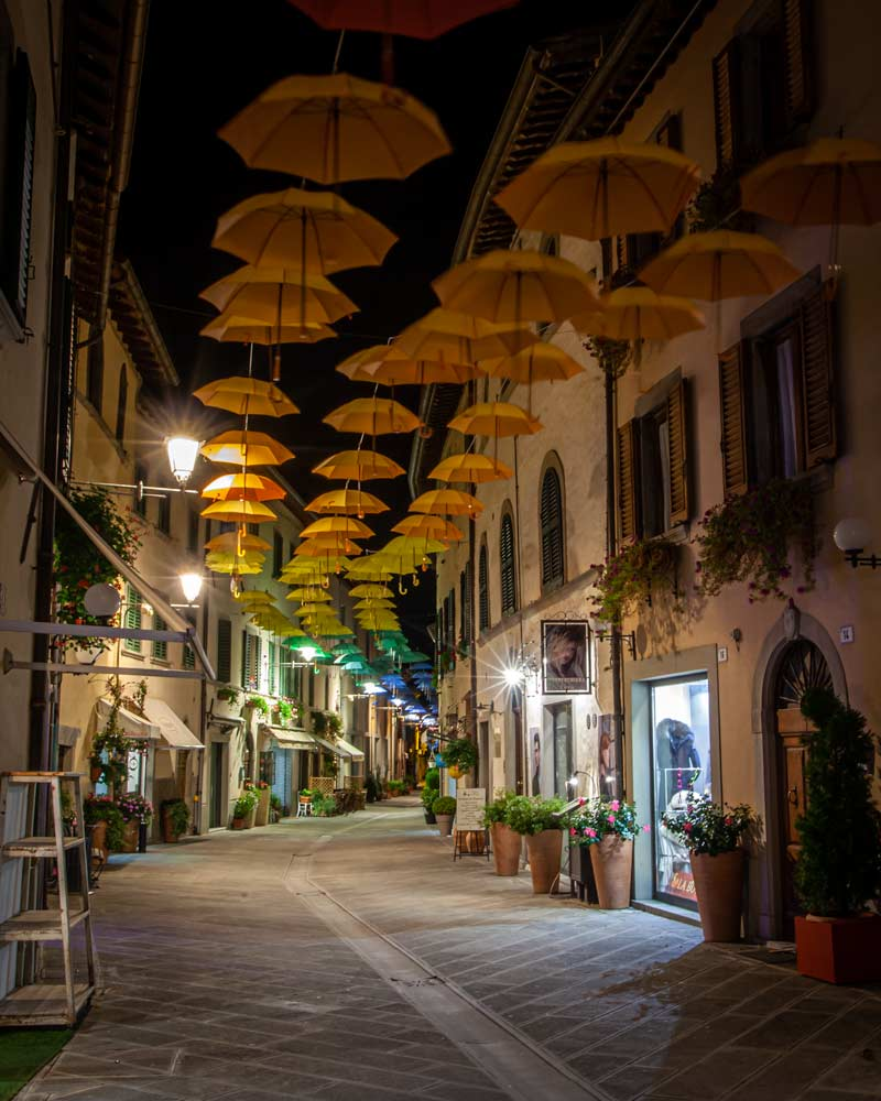 Bagno di Romagna by night with umbrellas hanging in a street