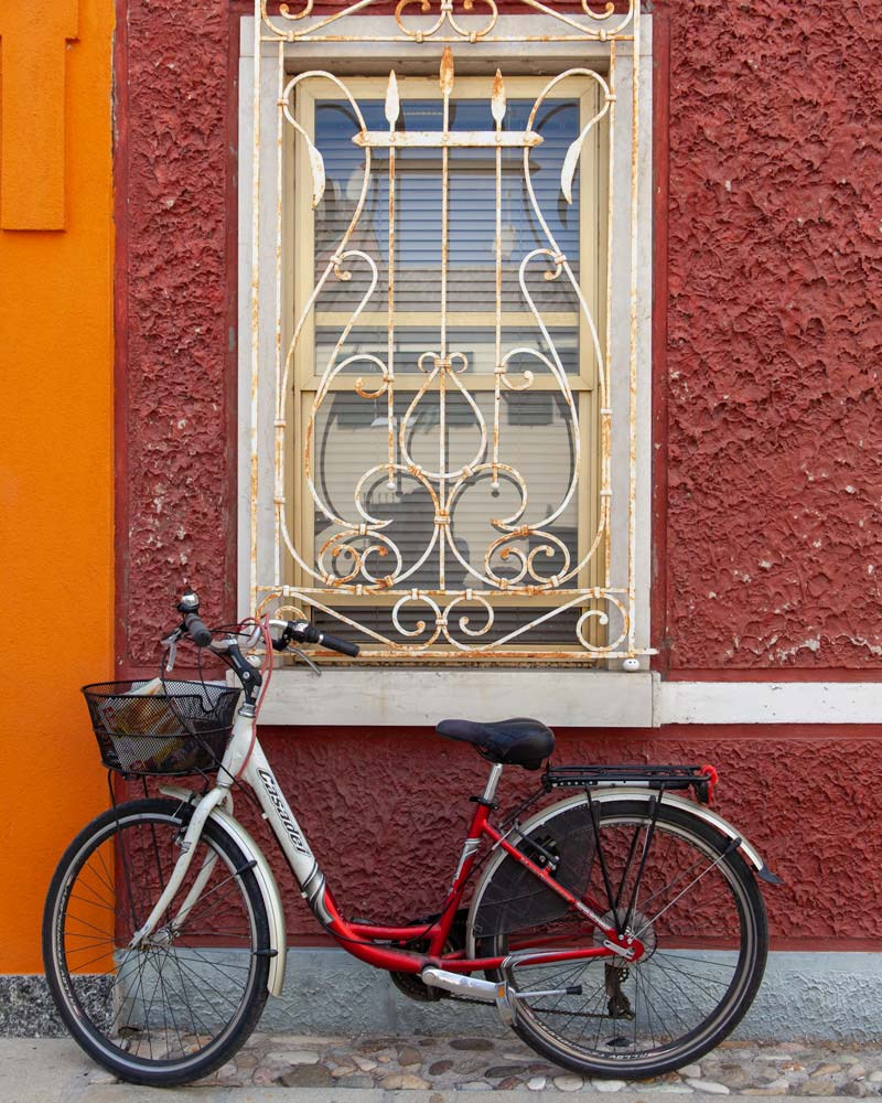 A red bike rests against a red wall with a white iron grill