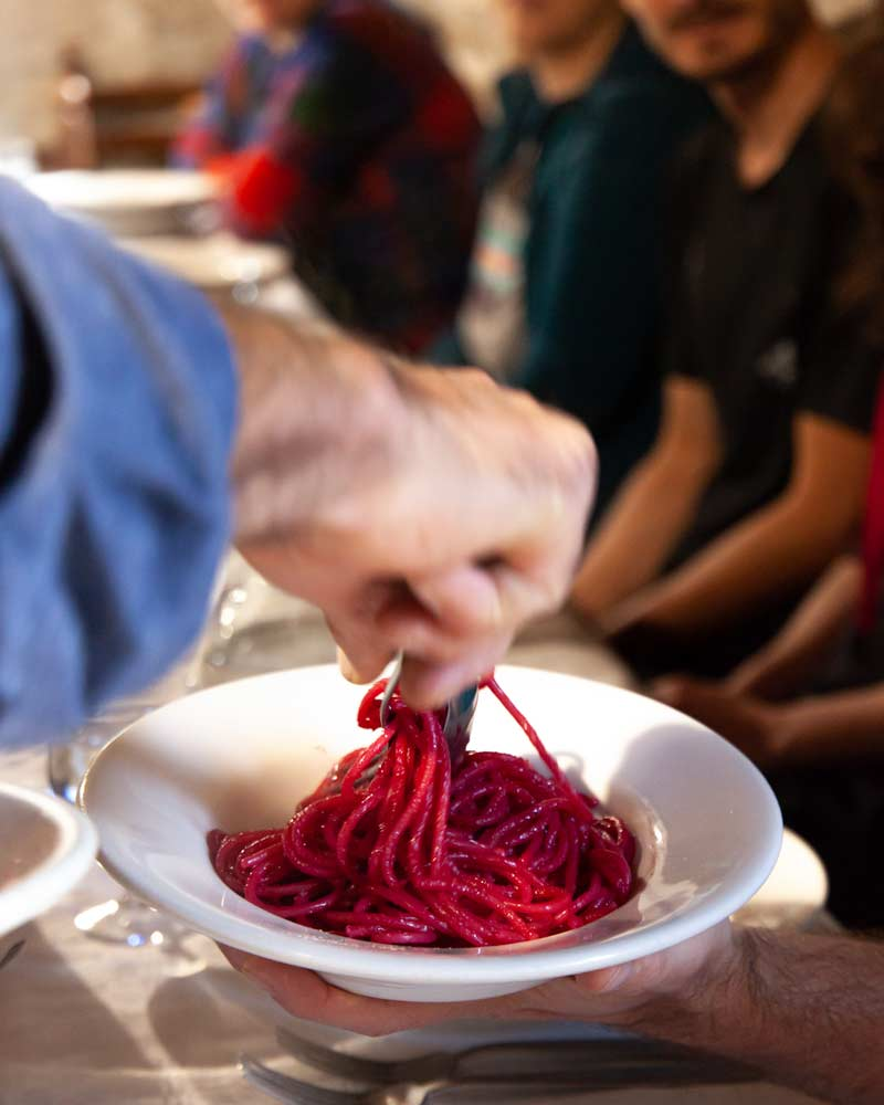 A plate of purple pasta, coloured from the beetroot it is boiled with, is dished out by the waiter