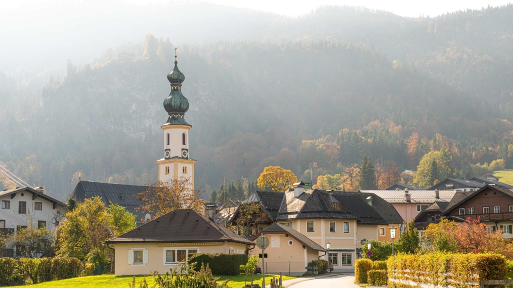 Beautiful mountain and lake views await in Saint Gilgen where a church spire stands infront of a towering mountain