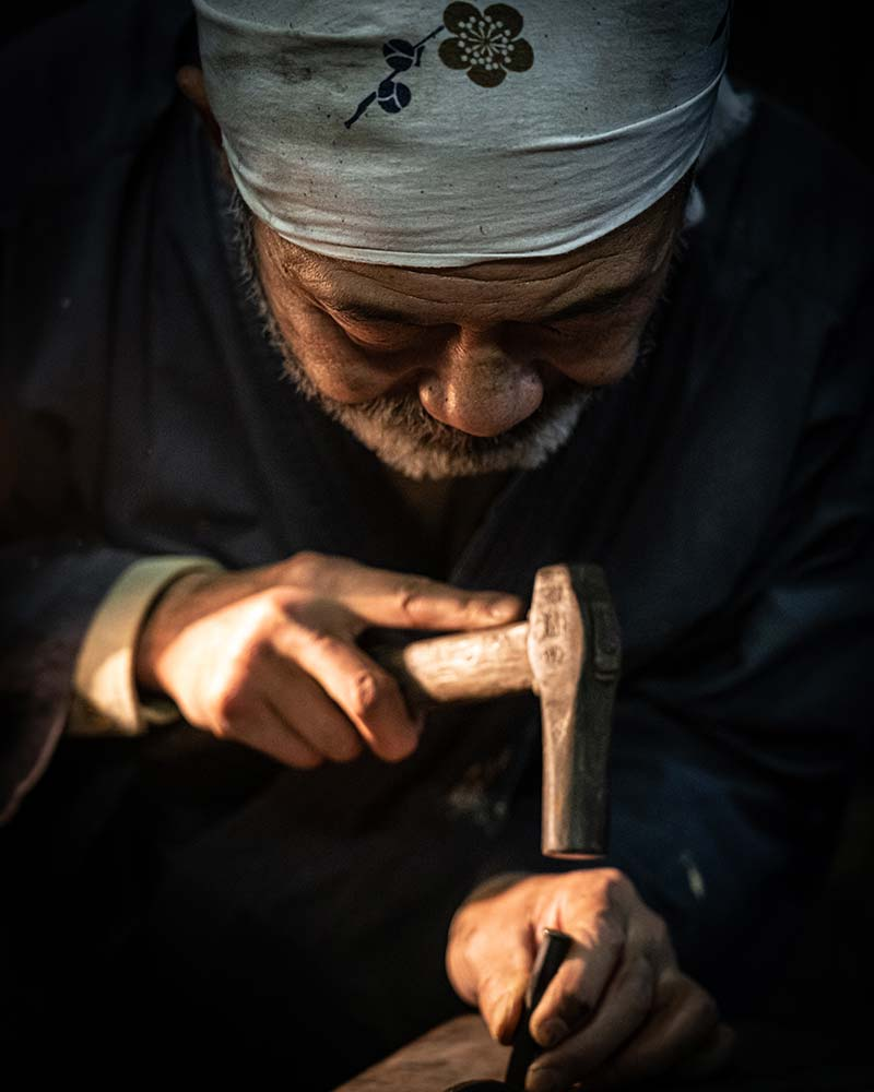 The blacksmith is hard at work hammering an etching into a freshly made knife in Kochi Japan