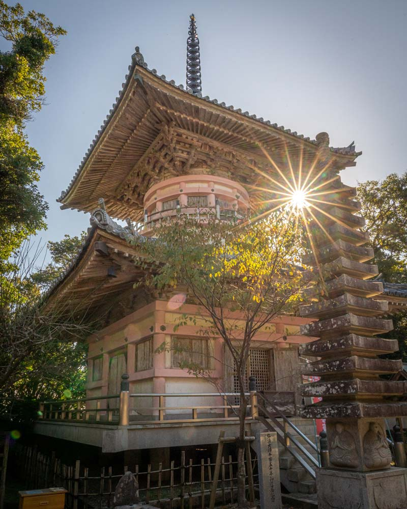 The sun shines behind a pink and white temple on the Shikou temple pilgrimage