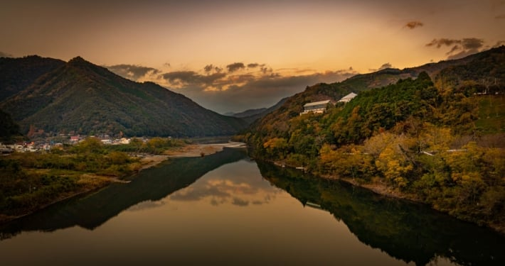 Sunset on the Shimanto river in Kochi Japan, with the mountains reflecting in the water