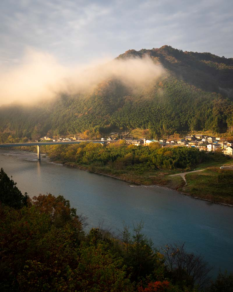 The Shimanto River at sunrise with clouds floating over the village