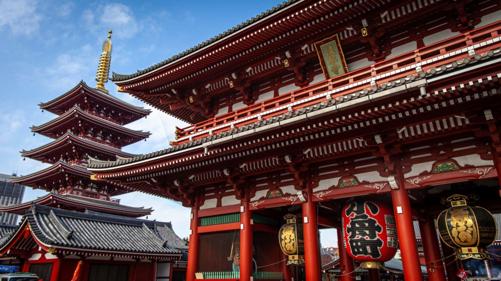 A beautiful red pagoda sits next to a large red temple in the city of Tokyo