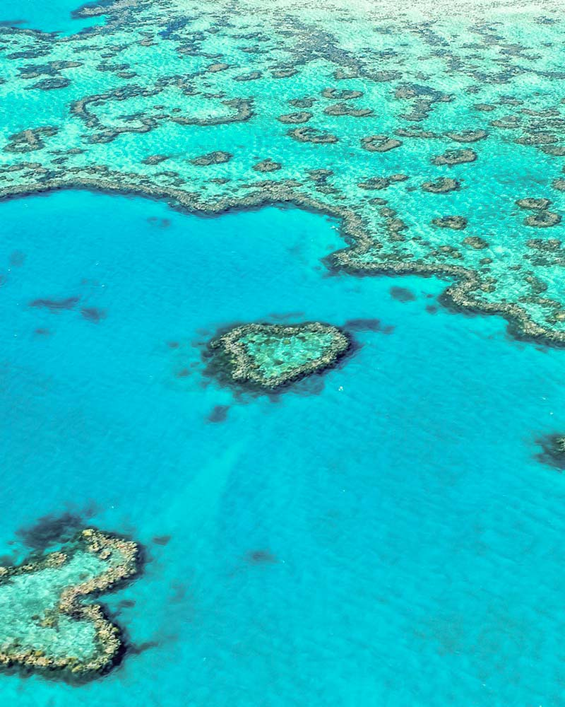 A heart shaped reef in the blue ocean from above