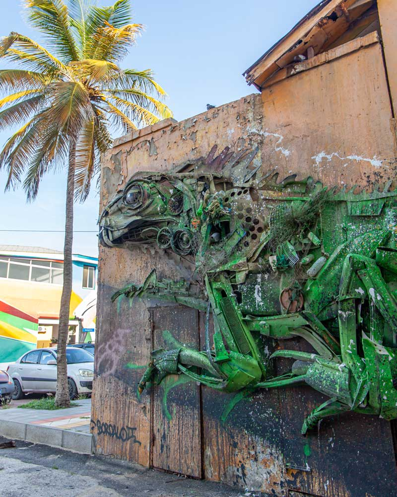Street art of a green iguana made of recycled materials in San Nicolas