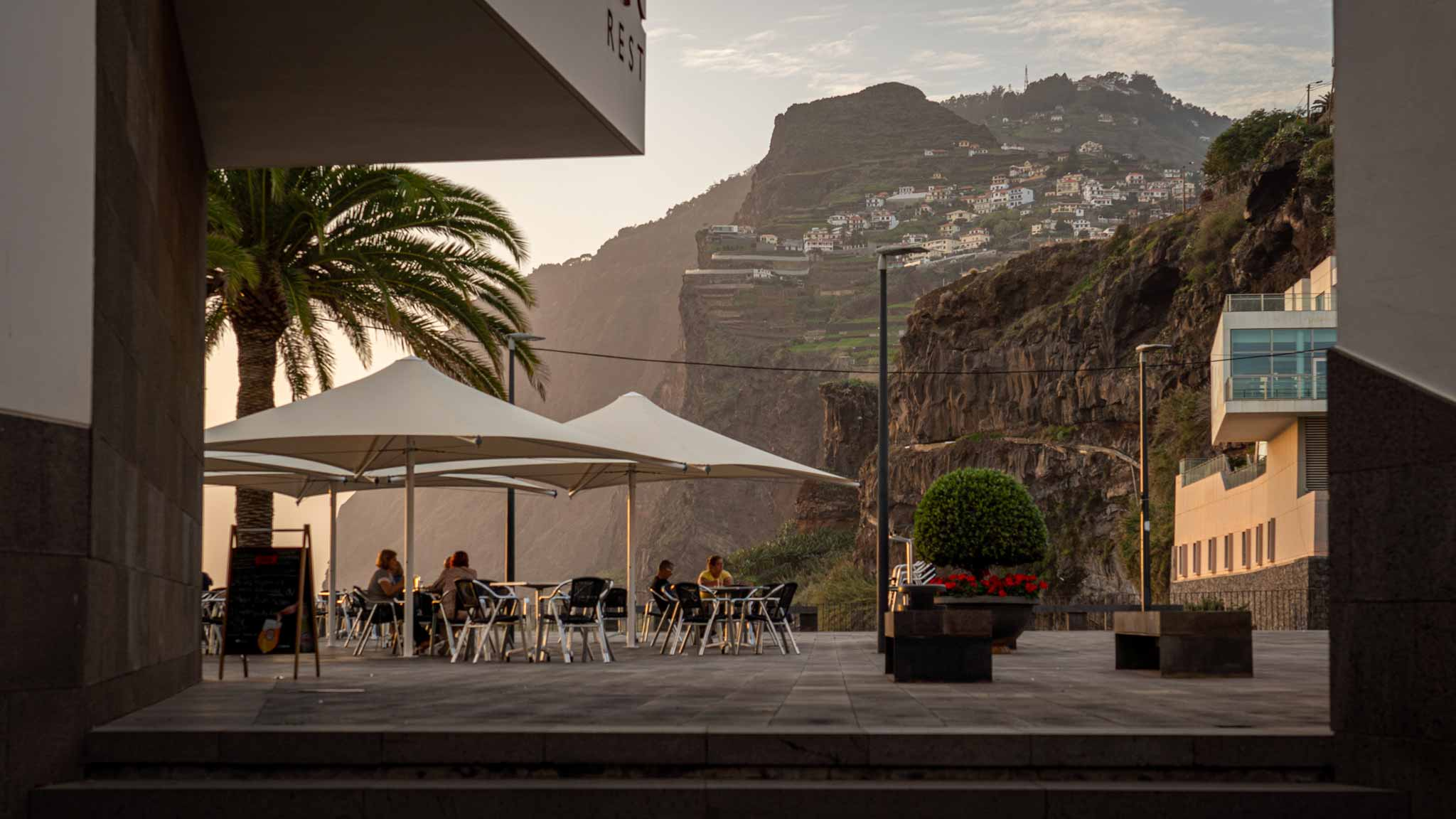 View from a restaurant in Camara do Lobos of a sea cliff at sunset