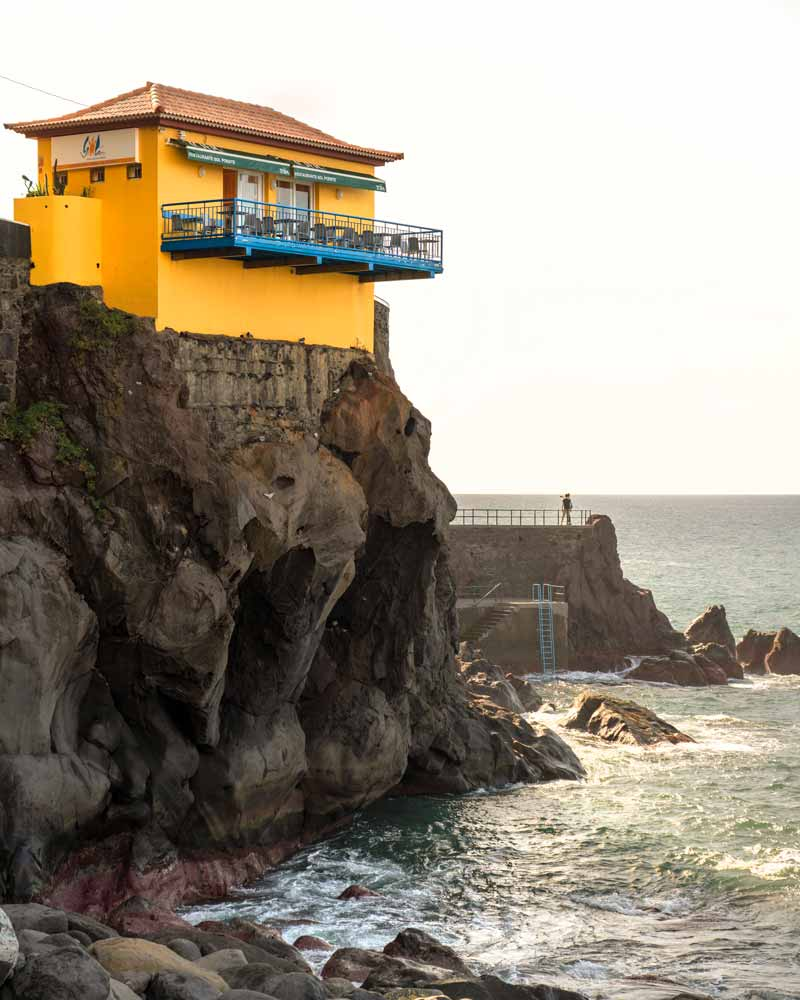 A bright yellow cafe perched on a cliff in Porto do Sol in Madeira