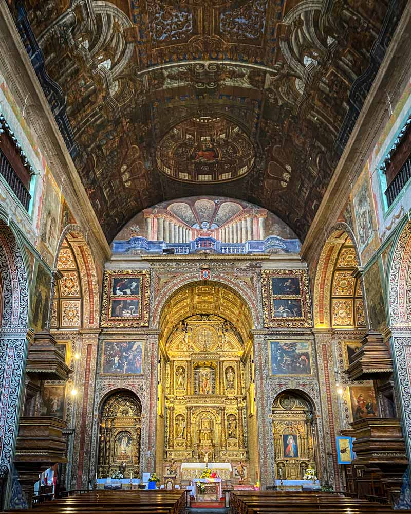 Inside a church with ornate gold and blue paintings and tiles, and a slightly curved ceiling with intricate wood work