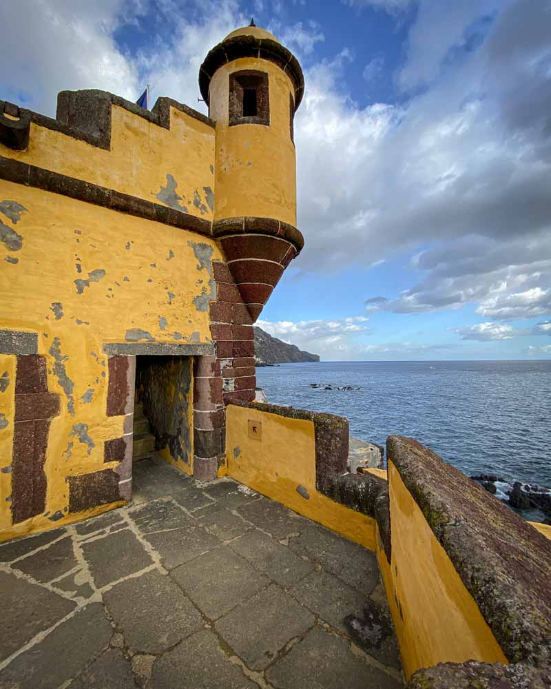 Funchal is home to many forts, and this bright yellow one with a turret sits on the oceans edge