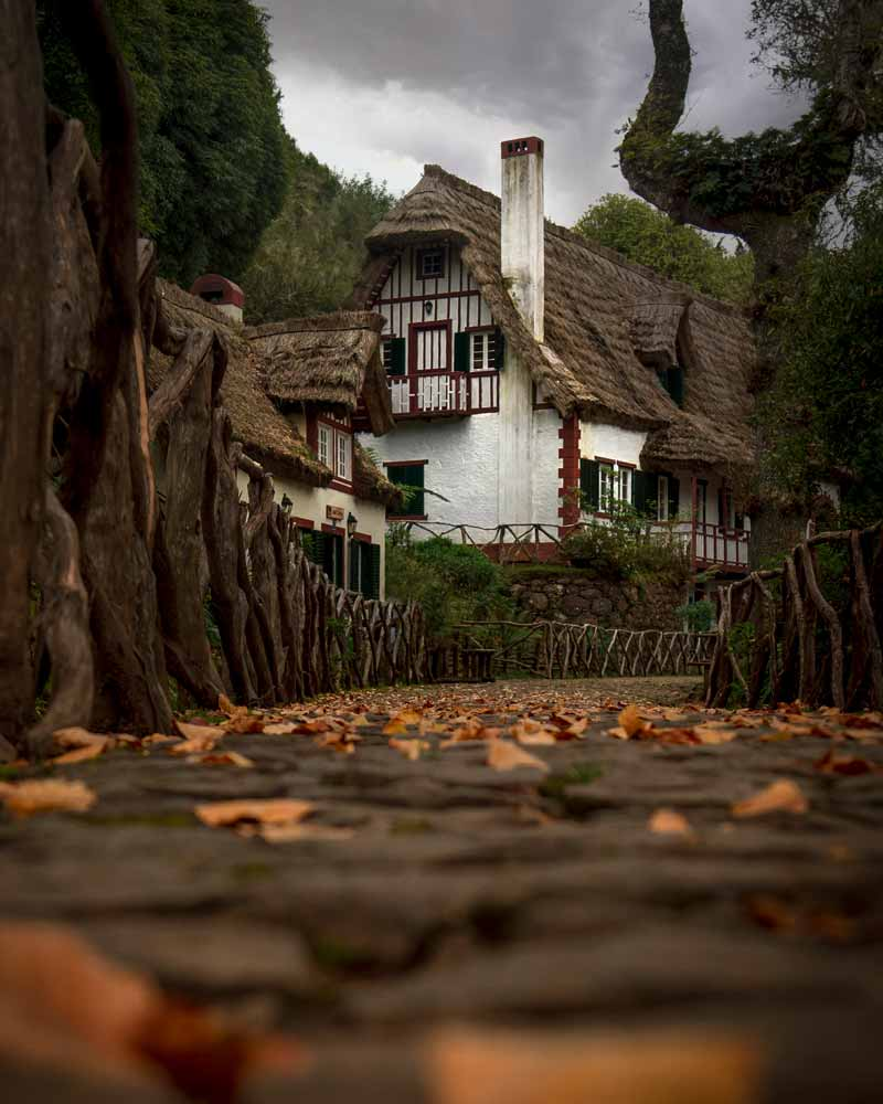 A tradtitional thatched house with autumn leaves and chimney at the start of the hiking trail
