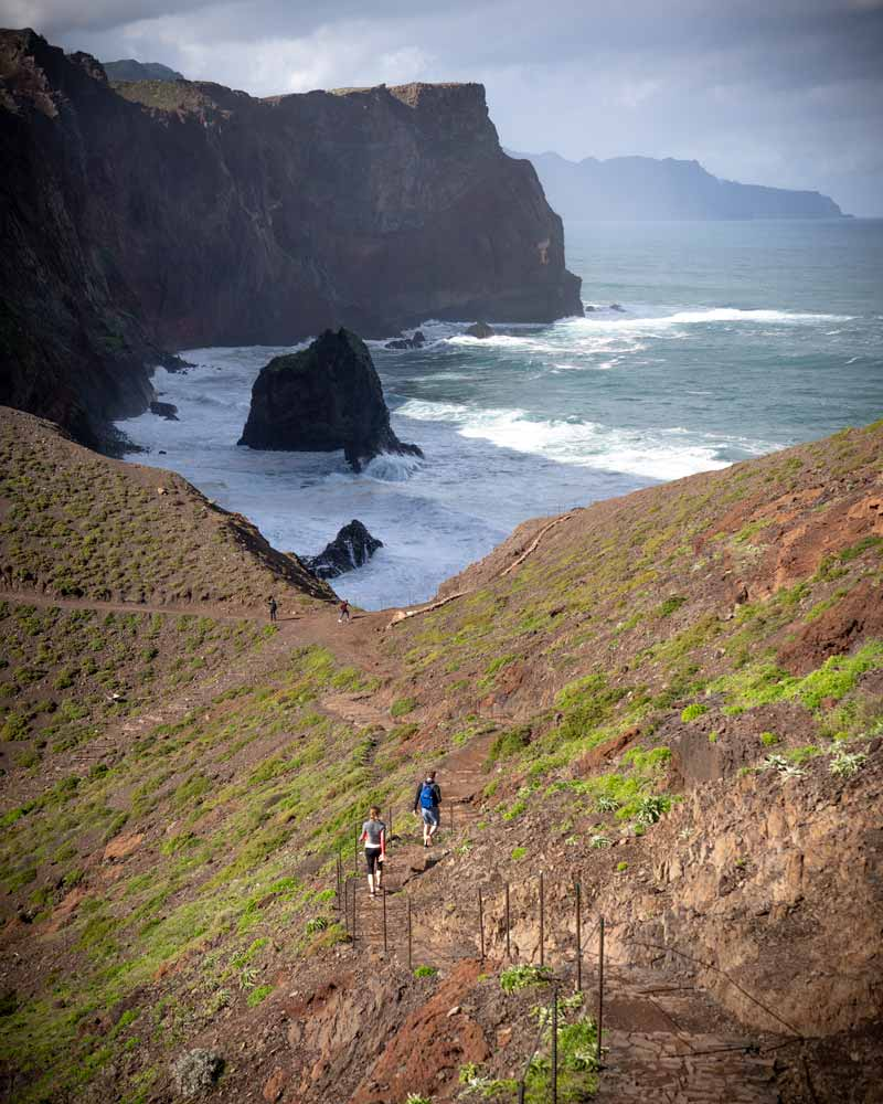 A couple climb the The trail out to Ponta de São Lourenço, with large swell against the cliffs below