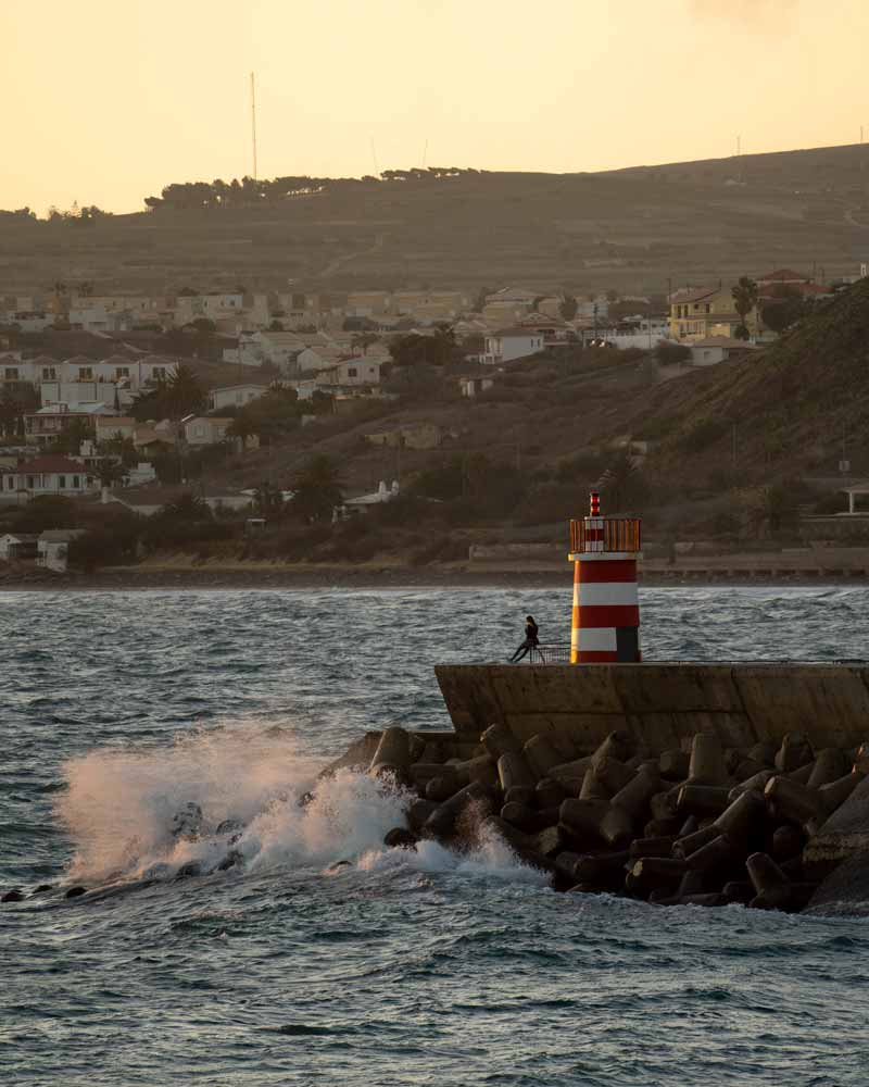 Sunset at the Porto Santo lighthouse with crashing waves