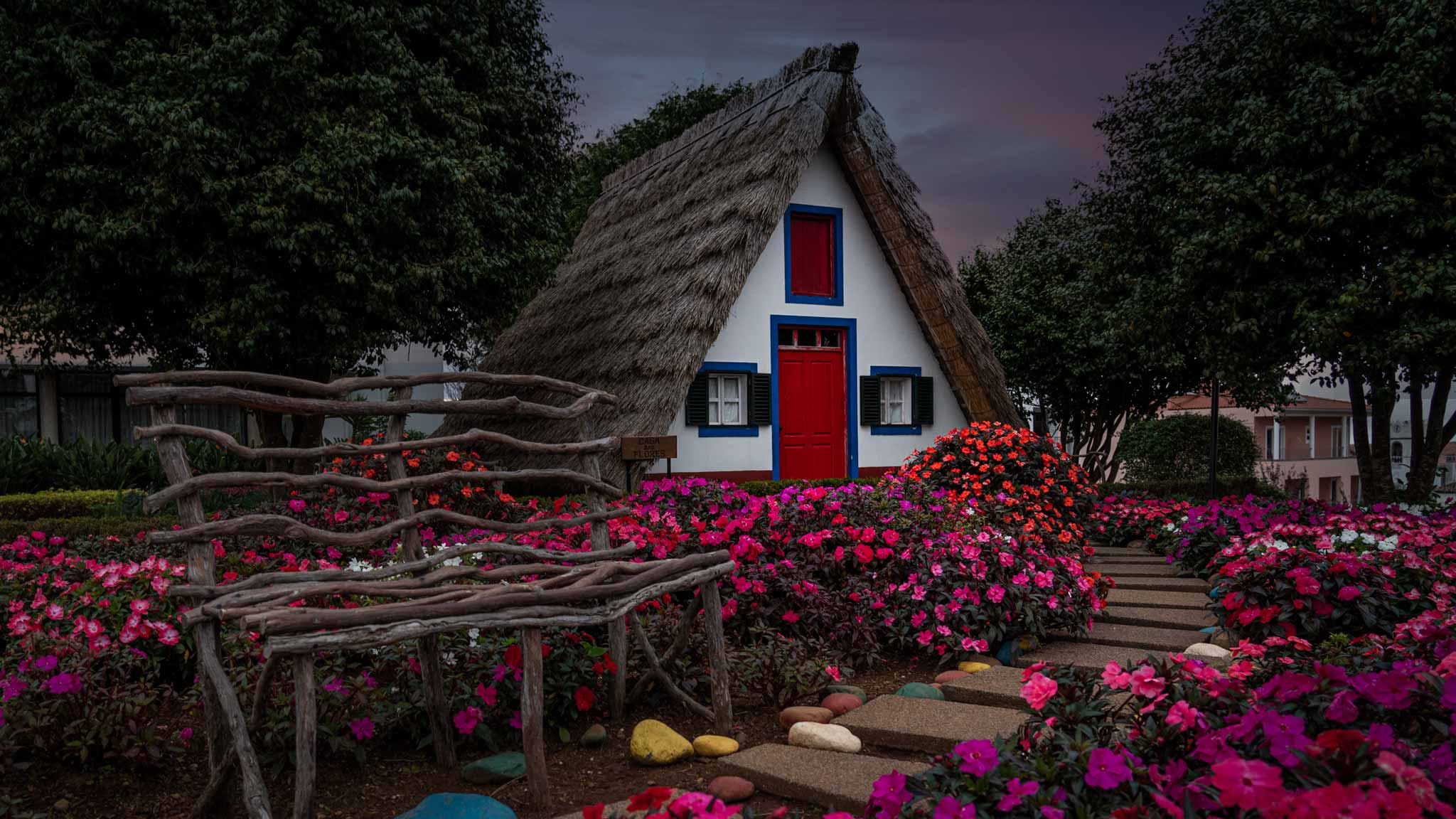 The traditional thatched houses of Santana, a pointed triangle shaped house with colourful blue and red windows and flowers outside