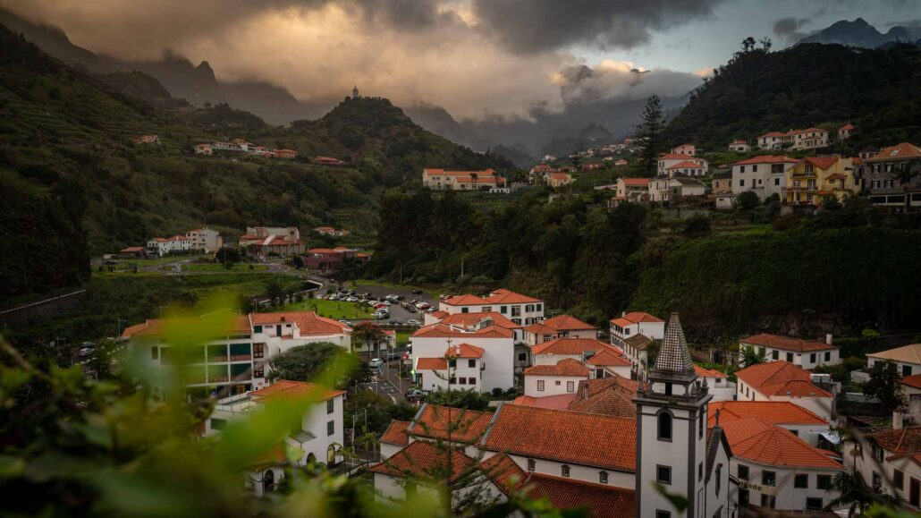 The municipality of Sao Vicente seen at sunset, with clouds floating around the mountains surrounding the town